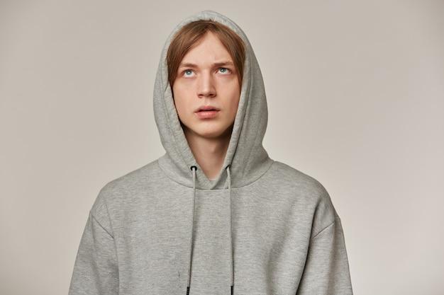 Ontevreden man, verveeld uitziende man met blond haar. ik draag een grijze hoodie, zet een capuchon op. rolt met zijn ogen. geërgerd over iets. mensen en emotie concept. stand geïsoleerd over grijze muur