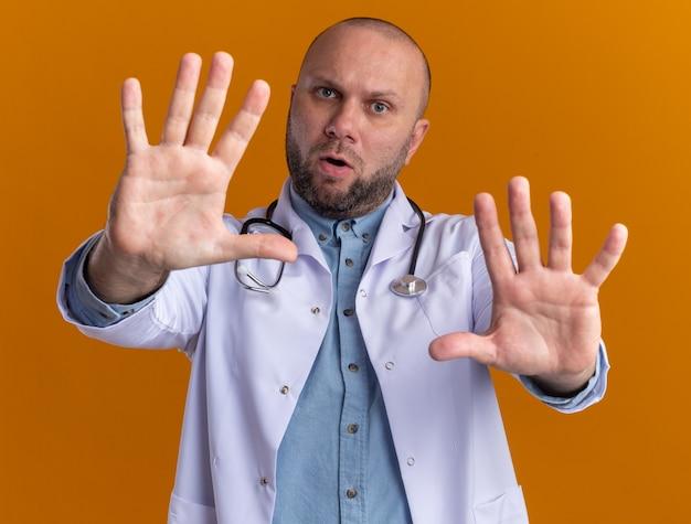 Ontevreden mannelijke arts van middelbare leeftijd met een medische mantel en een stethoscoop die een stopgebaar doet dat op een oranje muur is geïsoleerd