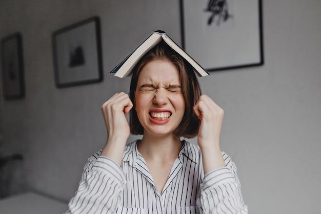 Ontevreden meisje in gestreept overhemd is boos met haar ogen dicht en open boek op haar hoofd tegen de achtergrond van de kamer met foto's.