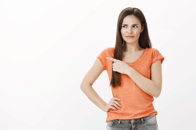 Ontevreden meisje krimpt ineen van iets slechts, wijst en kijkt teleurgesteld naar links
