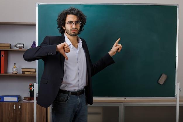 Ontevreden met duim omlaag jonge mannelijke leraar die een bril draagt, wijst naar het bord in de klas