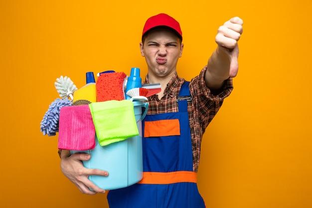 Ontevreden met duim omlaag jonge schoonmaakster met uniform en dop met emmer met schoonmaakgereedschap