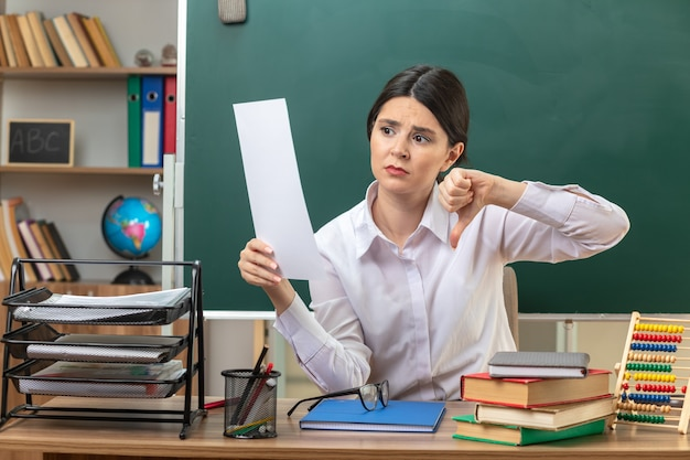 Ontevreden met duim omlaag jonge vrouwelijke leraar die vasthoudt en kijkt naar papier dat aan tafel zit met schoolhulpmiddelen in de klas