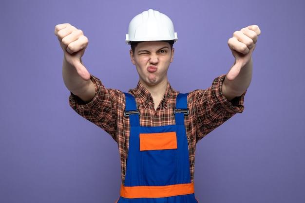 Ontevreden met duimen naar beneden jonge mannelijke bouwer die uniform draagt