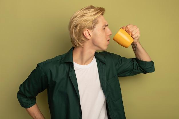Ontevreden met gesloten ogen drinkt de jonge blonde kerel die een groen t-shirt draagt thee