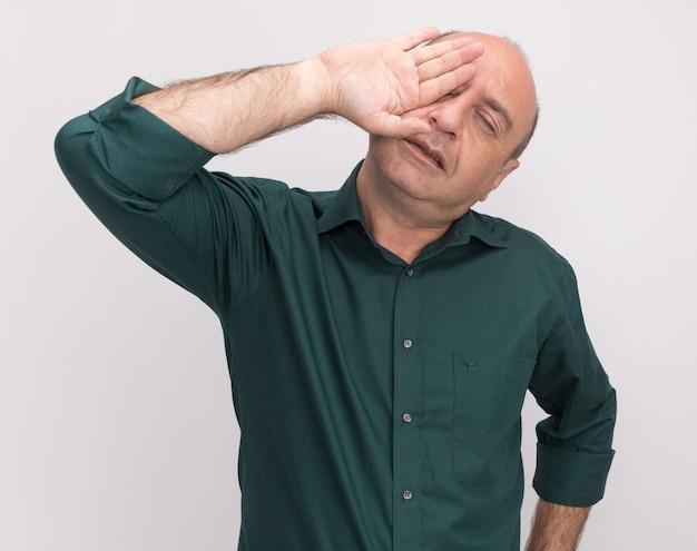 Ontevreden met gesloten ogen hoofd kantelen man van middelbare leeftijd met groen t-shirt bedekt oog met hand geïsoleerd op een witte muur