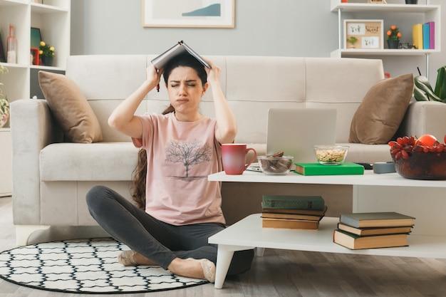 Ontevreden met gesloten ogen jong meisje bedekt hoofd met notitieboekje zittend op de vloer achter salontafel in woonkamer