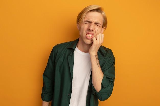 Ontevreden met gesloten ogen jonge blonde kerel die groen t-shirt draagt dat hand op wang zet