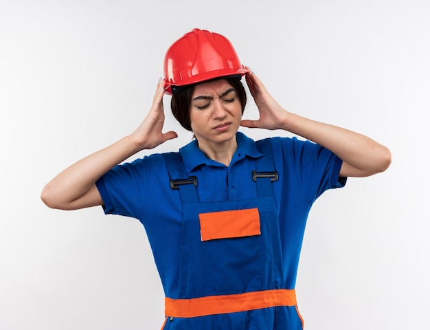 Ontevreden met gesloten ogen jonge bouwvrouw in uniform hand in hand rond het hoofd