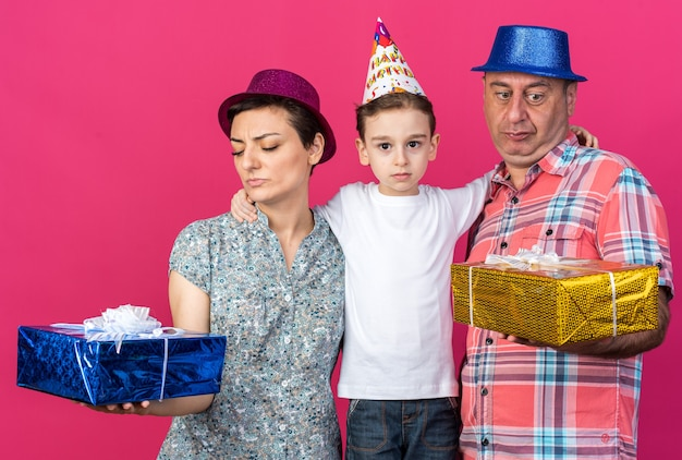 Ontevreden moeder en vader met feestmutsen die geschenkdozen vasthouden en bekijken die bij hun zoon staan geïsoleerd op roze muur met kopieerruimte