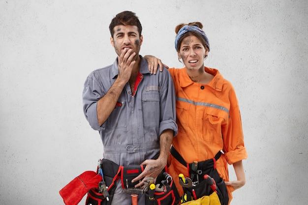 Ontevreden monteurs repareren kabellijnen, hebben vuile gezichten na hard werken