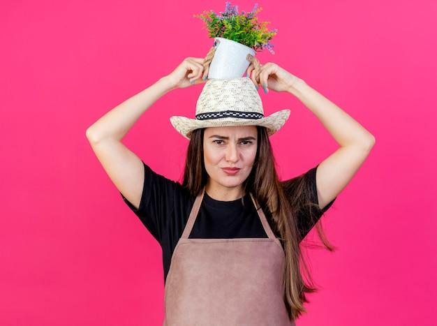 Ontevreden mooi tuinman meisje in uniform dragen tuinieren hoed bloem zetten bloempot op hoofd geïsoleerd op roze