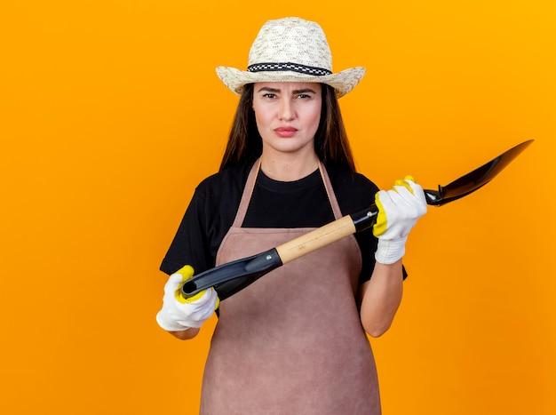Ontevreden mooi tuinman meisje uniform dragen en tuinieren hoed met handschoenen houden schop geïsoleerd op een oranje achtergrond