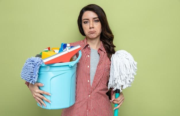 Ontevreden mooie blanke schonere vrouw met schoonmaakapparatuur en mob