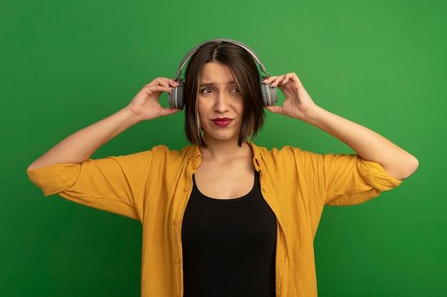 Ontevreden mooie blanke vrouw die op koptelefoon kant op groen kijkt