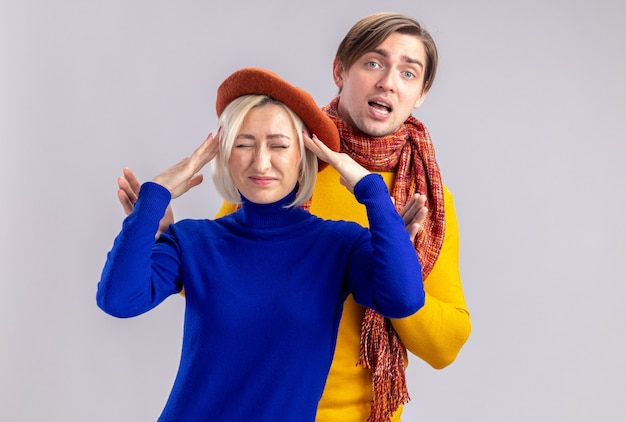 Ontevreden mooie blonde vrouw met baret die handen op haar hoofd legt en voor een knappe slavische man staat met sjaal om zijn nek