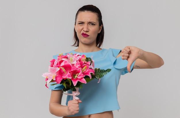 Ontevreden mooie jonge vrouw die een boeket bloemen vasthoudt en naar beneden wijst