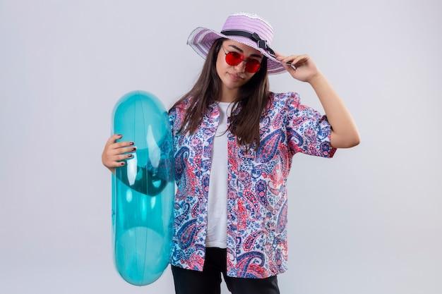 Ontevreden mooie vrouw die de zomerhoed en rode zonnebril draagt die opblaasbare ring houdt wat betreft haar hoed over geïsoleerde witte muur