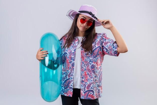 Ontevreden mooie vrouw die zomerhoed en rode zonnebril draagt die opblaasbare ring houdt die haar hoed status raakt