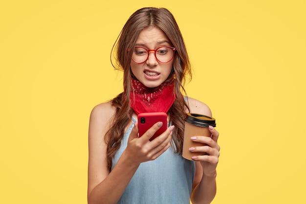 Ontevreden mooie vrouw kijkt met walging en afkeer naar mobiel, bewerkt foto in speciale app, drinkt koffie om mee te nemen, poseert voor gele muur, heeft een hekel aan, verbonden met supersnel internet