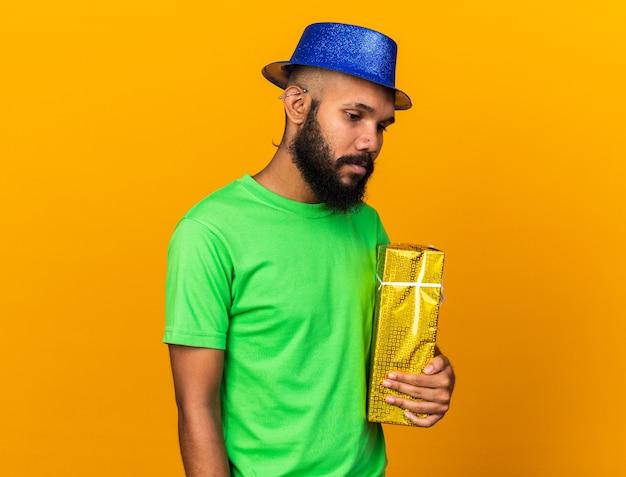 Ontevreden naar beneden kijkende jonge afro-amerikaanse man met een feestmuts met een geschenkdoos