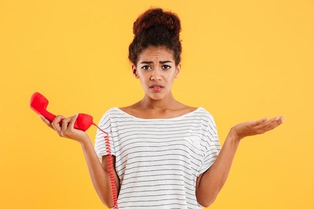 Ontevreden ongelukkige dame die rode zaktelefoon houdt terwijl geïsoleerd status