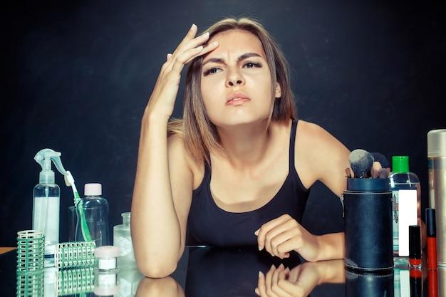 Ontevreden ongelukkige jonge vrouw die haar zelf in spiegel op zwart bekijkt. roblem huid en acne concept