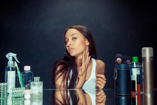 Ontevreden ongelukkige jonge vrouw die haar zelf in spiegel op zwarte studioachtergrond bekijkt. roblem huid en acne concept. ochtend, make-up en menselijke emotiesconcepten. kaukasisch model in de studio