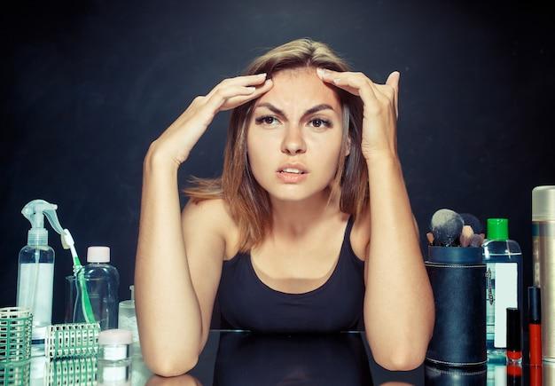 Ontevreden ongelukkige jonge vrouw die haar zelf in spiegel op zwarte studioachtergrond bekijkt. roblem huid en acne concept. ochtend, make-up en menselijke emotiesconcepten