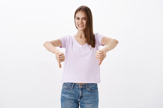 Ontevreden ontevreden aantrekkelijke jonge vrouwelijke klant in blouse en spijkerbroek met duimen naar beneden onhandig glimlachen terwijl negatieve feedback en afwijzing slecht idee over witte muur geeft