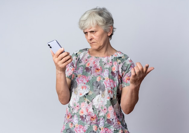 Ontevreden oudere vrouw houdt en kijkt naar telefoon geïsoleerd op een witte muur