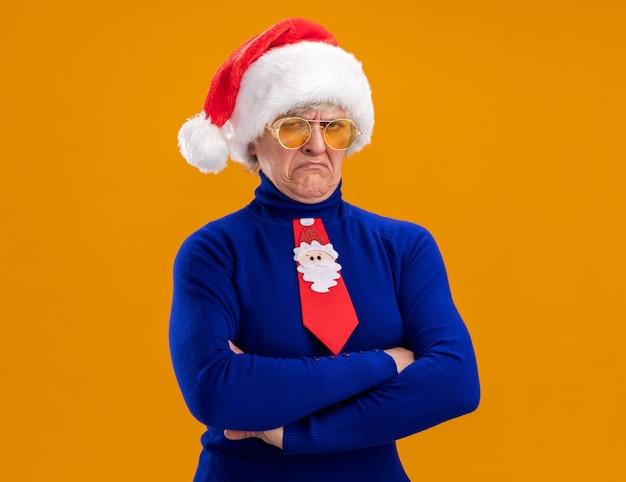Ontevreden oudere vrouw in zonnebril met kerstmuts en kerststropdas staande met gekruiste armen geïsoleerd op oranje muur met kopieerruimte