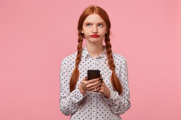Ontevreden roodharig meisje met twee vlechten die zonder enthousiasme in de linkerbovenhoek kijken en proberen te bedenken wat ze moet schrijven in een bericht aan haar vriend die de telefoon in haar handen houdt, op een roze muur