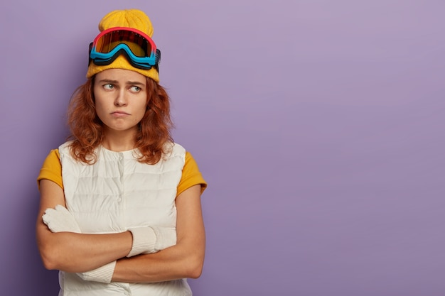 Ontevreden roodharige vrouw houdt handen gekruist, fronst gezicht, is in een slecht humeur, draagt skibril en wit vest, ontevredenheid, geïsoleerd op paarse achtergrond.