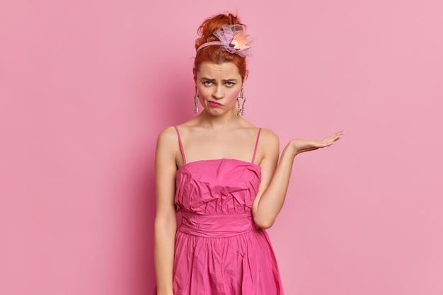 Ontevreden roodharige vrouw kijkt met beledigde droevige uitdrukking op camera verhoogt palm houdt niet van iets