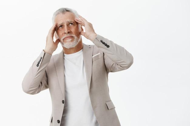 Ontevreden senior zakenman hand in hand op het hoofd en op zoek gehinderd, hard geluid klagen