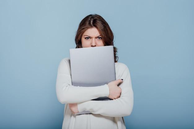 Ontevreden stijlvolle vrouw fronsen terwijl knuffelen laptop geïsoleerd tegen blauwe muur