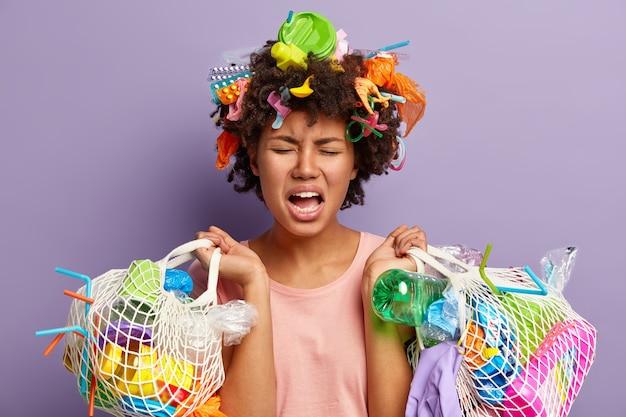 Ontevreden, stressvolle afro-amerikaanse vrouw houdt twee tassen vol vuilnis vast, huilt van negatieve emoties, is moe na het verzamelen van afval, bezorgd en verontrust over ecologische problemen