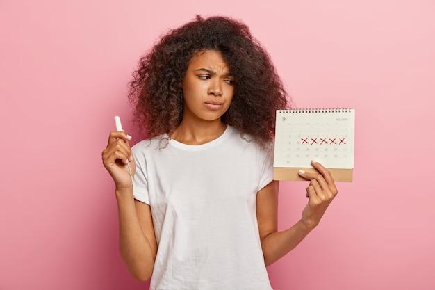 Ontevreden stressvolle donkere vrouw kijkt naar periodekalender met gemarkeerde rode kruisen