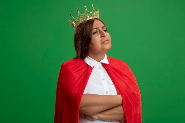 Ontevreden superheld vrouw van middelbare leeftijd kijken naar kant dragen kroon kruising handen geïsoleerd op groene achtergrond