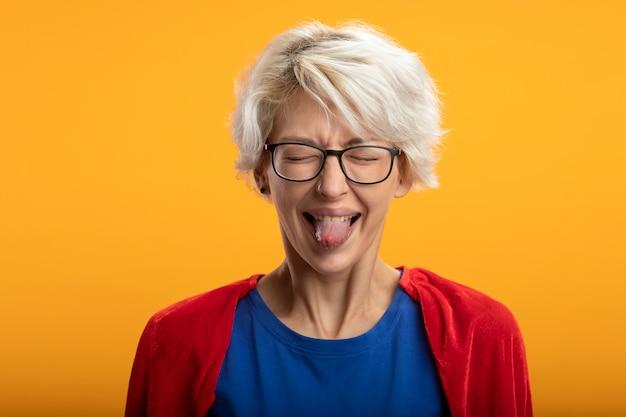 Ontevreden supervrouw met rode cape in optische glazen steekt tong uit die op oranje muur wordt geïsoleerd