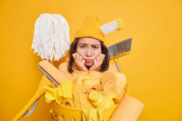 Ontevreden trieste vrouw wil de kamer niet opruimen kijkt verdrietig naar rotzooi en vuil gebruikt verschillende schoonmaakgereedschappen in de buurt van wasmand tegen gele muur