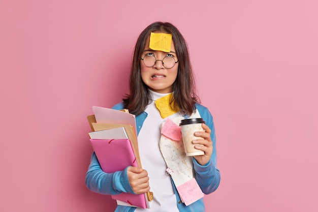 Ontevreden universiteitsstudent bijt op lippen en kijkt met een ongelukkige vermoeide uitdrukking naar boven, drinkt afhaalmaaltijden koffie werkt met papieren draagt een ronde bril.