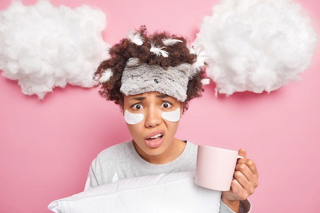 Ontevreden verbaasde jonge vrouw heeft veren in slordig haar geniet van een verse kop koffie houdt kussen geïsoleerd over roze muur