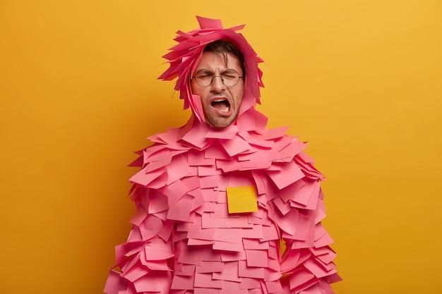 Ontevreden, vermoeide man gaapt, opent zijn mond en houdt zijn ogen dicht, draagt een outfit met plakbriefjes, heeft lol of dwazen rond, poseert over een felgele muur. man bedekt met stickers op het lichaam en boven het hoofd