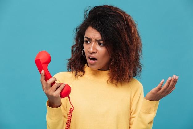 Ontevreden verwarde jonge afrikaanse vrouw die telefonisch spreekt.