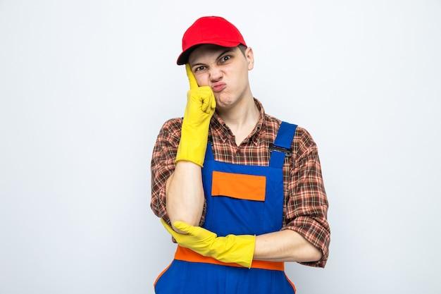 Ontevreden vinger op de wang te leggen, jonge schoonmaakster die uniform en pet met handschoenen draagt