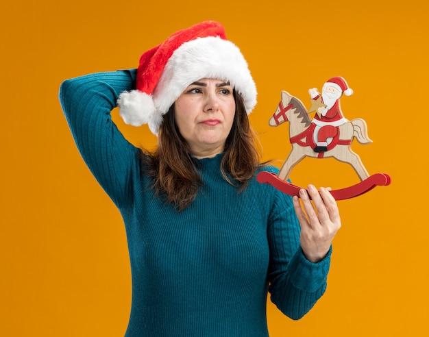Ontevreden volwassen blanke vrouw met kerstmuts houden en kijken naar santa op hobbelpaard decoratie geïsoleerd op een oranje achtergrond met kopie ruimte