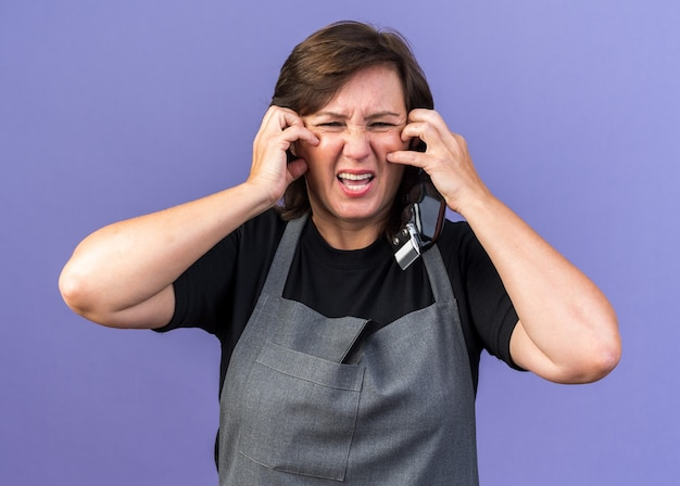 Ontevreden volwassen blanke vrouwelijke kapper in uniform krabbend gezicht met handen met tondeuse geïsoleerd op paarse muur met kopieerruimte Gratis Foto