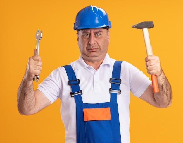 Ontevreden volwassen bouwersmens in uniform houdt moersleutel en hamer die op oranje muur wordt geïsoleerd